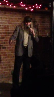 "on  stage at ""Nutt Street""comedy club"