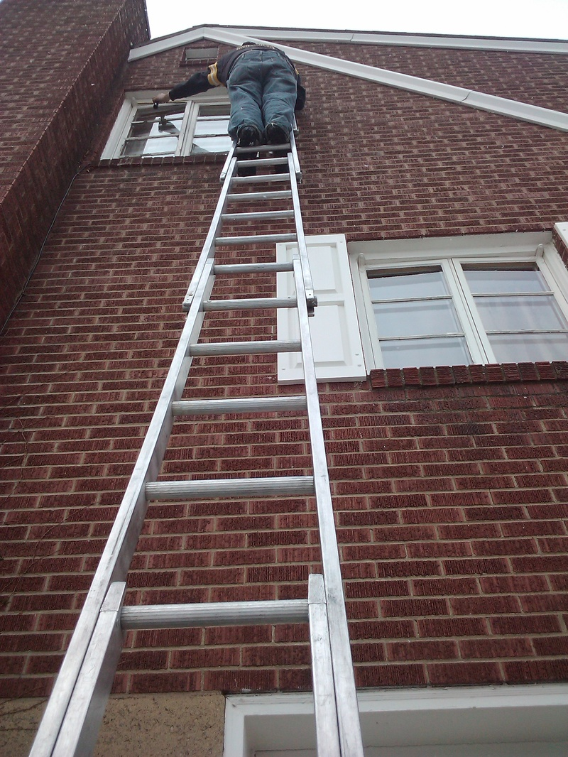 Robert cleaning a 3rd story, 6 panel window