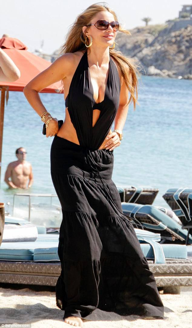 all-black ensemble consisting of a cleavage-heavy cut-out bikini top beneath a maxi skirt that gripped her waist before flowing to the ground, covering her feet.