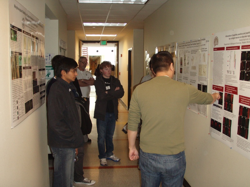 Graduate students describing their posters