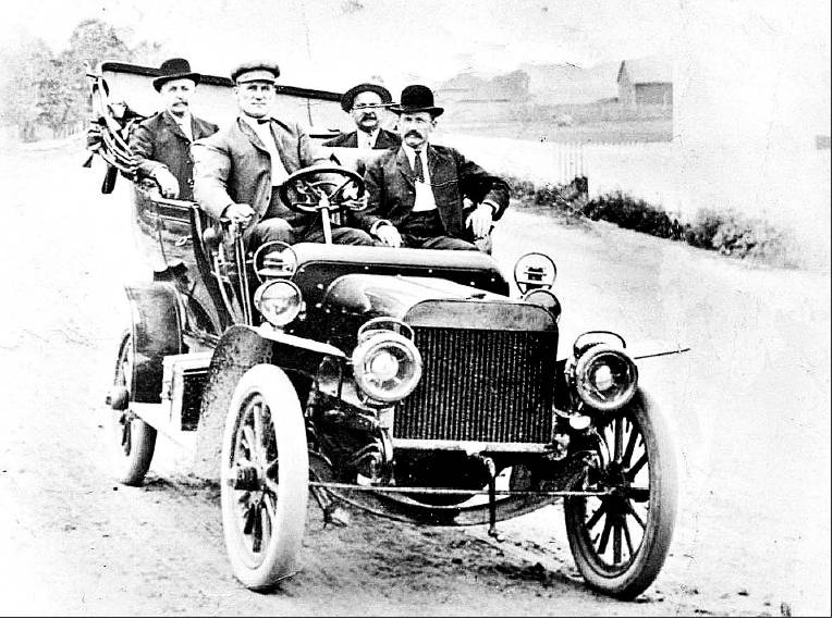 Frank James in front seat with mustache.