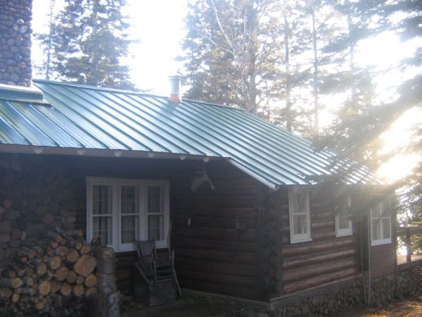 A log cabin with a new metal roof Cabins with metal roofs